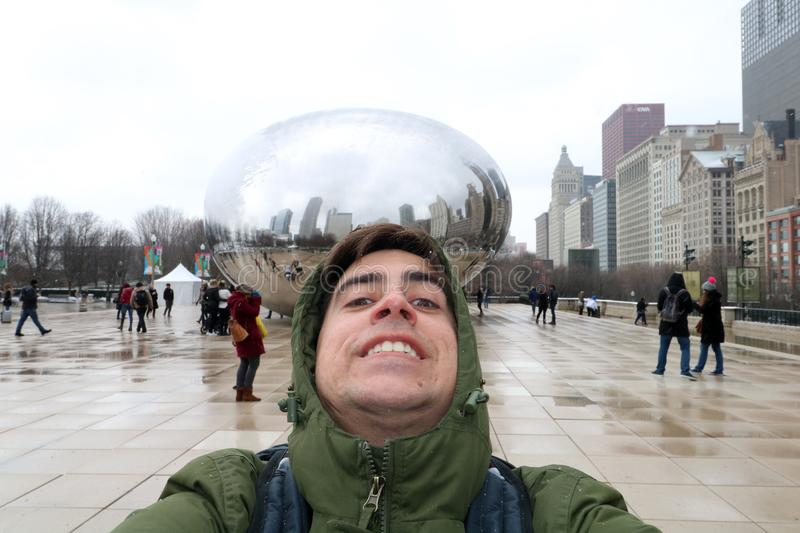 Funny tourist at Cloud gate at Chicago Illinois Bean mirror art with people and buildings. royalty free stock image