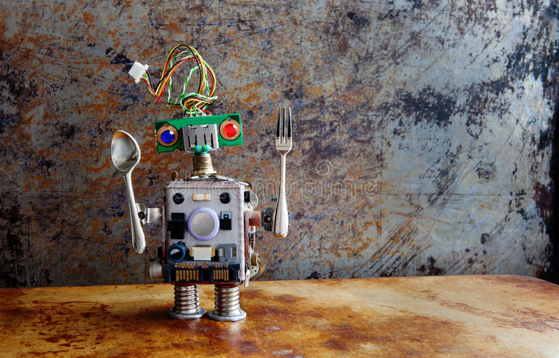 Funny toy robot with spoon fork standing on rusty textured backdrop, vintage grunge metallic wall background royalty free stock photos