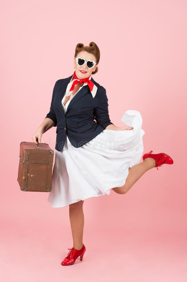 Funny traveler girl with suitcase and black sunglasses. Brunette woman in pin-up style with vintage case. stock image