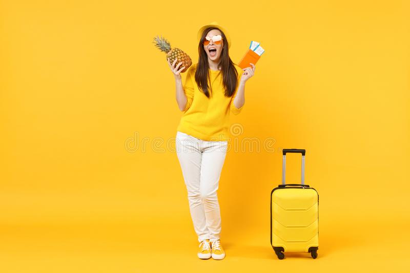 Funny traveler tourist woman in hat hold passport, tickets, fresh ripe pineapple fruit isolated on yellow orange. Background. Passenger traveling abroad on stock photos