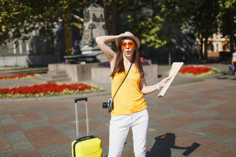 Funny traveler tourist woman in yellow clothes, orange heart glasses with suitcase city map photo camera in city outdoor stock photography