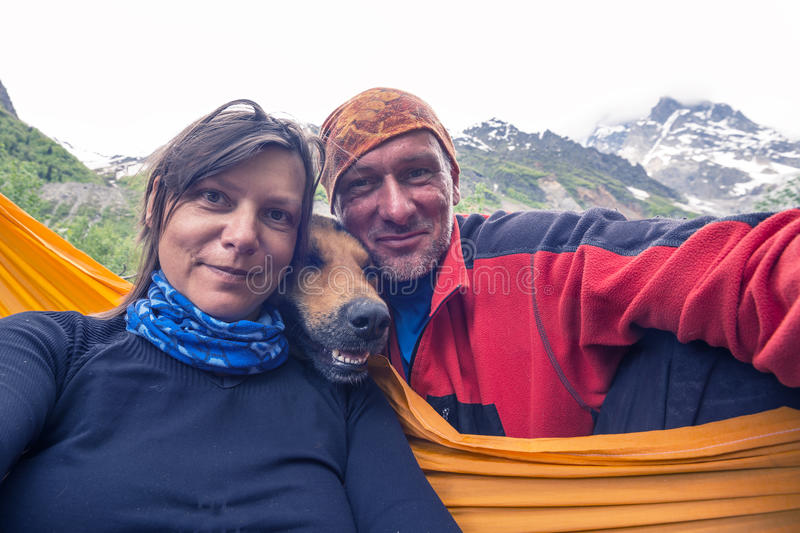 Funny travelers with big smiling dog, taking selfie on the mount royalty free stock image