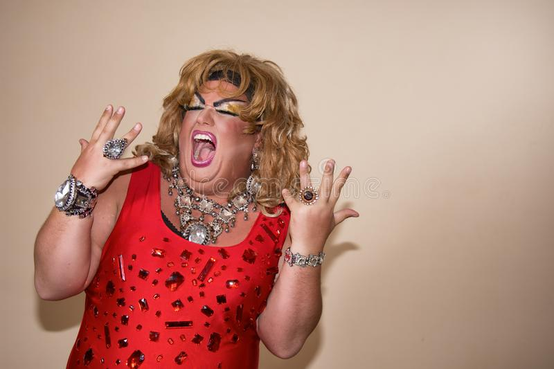 Funny travesty actor. Drag queen in red. Feelings and emotions. Funny travesty actor. Drag queen. Fat man and make-up stock photo