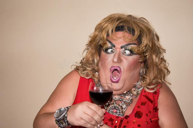 Funny travesty actor. Drag queen and red wine. Feelings and emotions. Funny travesty actor. Drag queen. Fat man and make-up stock photos