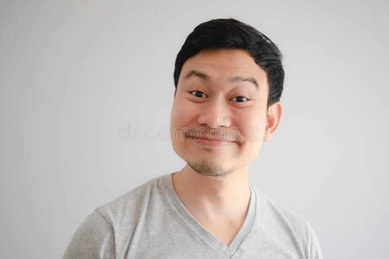 Funny tricky awkward smirk face of man in grey t-shirt royalty free stock image