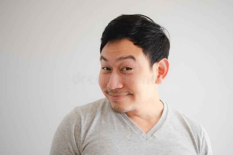Funny tricky awkward smirk face of man in grey t-shirt royalty free stock photos