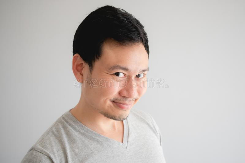 Funny tricky awkward smirk face of man in grey t-shirt royalty free stock photography