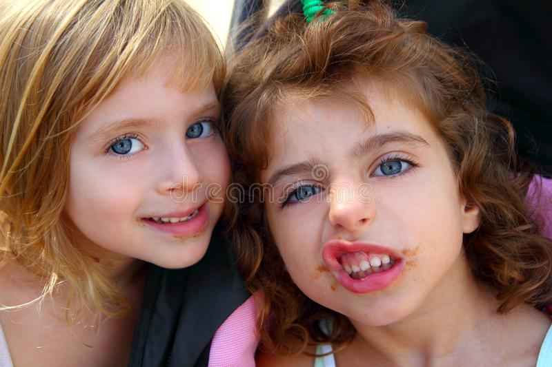 Funny two little sister girls funny face gesture. Dirty mouth royalty free stock image