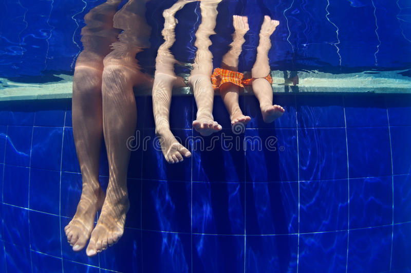 Funny underwater photo mother with kids legs in swimming pool royalty free stock images
