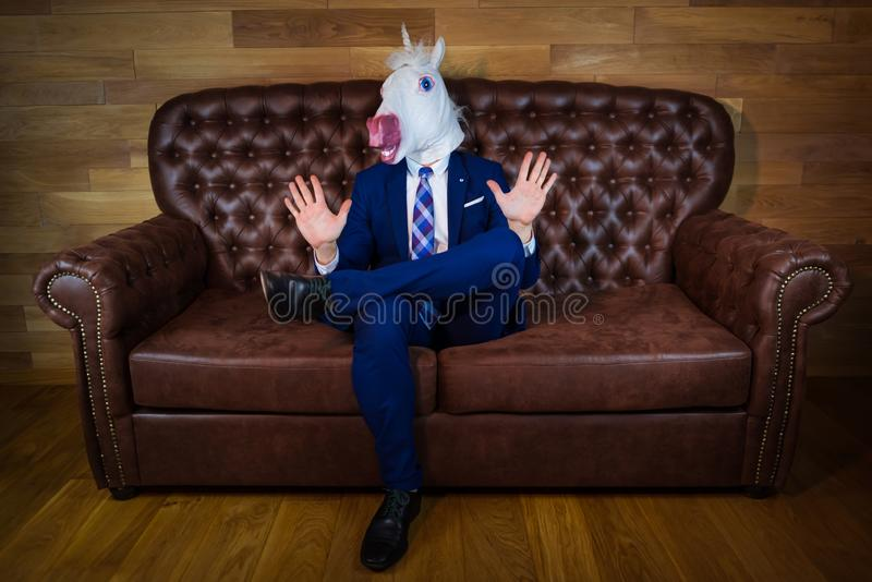 Funny unicorn in elegant suit siting on sofa royalty free stock images