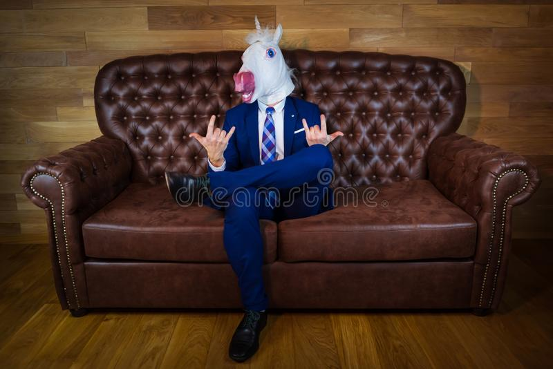 Funny unicorn in elegant suit sits on sofa like a boss and showing rock gesture stock image
