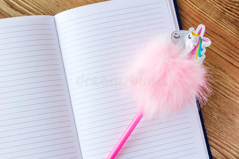 Funny unicorn pen on lined blank notebook royalty free stock images