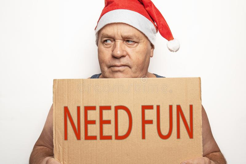 Funny upset and angry mature man in red Christmas Santa hat holds cardboard sign with inscription - need fun on white background royalty free stock photo