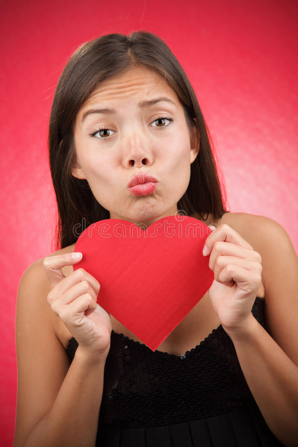 Funny Valentines Day woman alone. Valentines day alone? Woman looking for love holding a Valentines Day heart sign. Beautiful mixed race asian / caucasian model royalty free stock photos