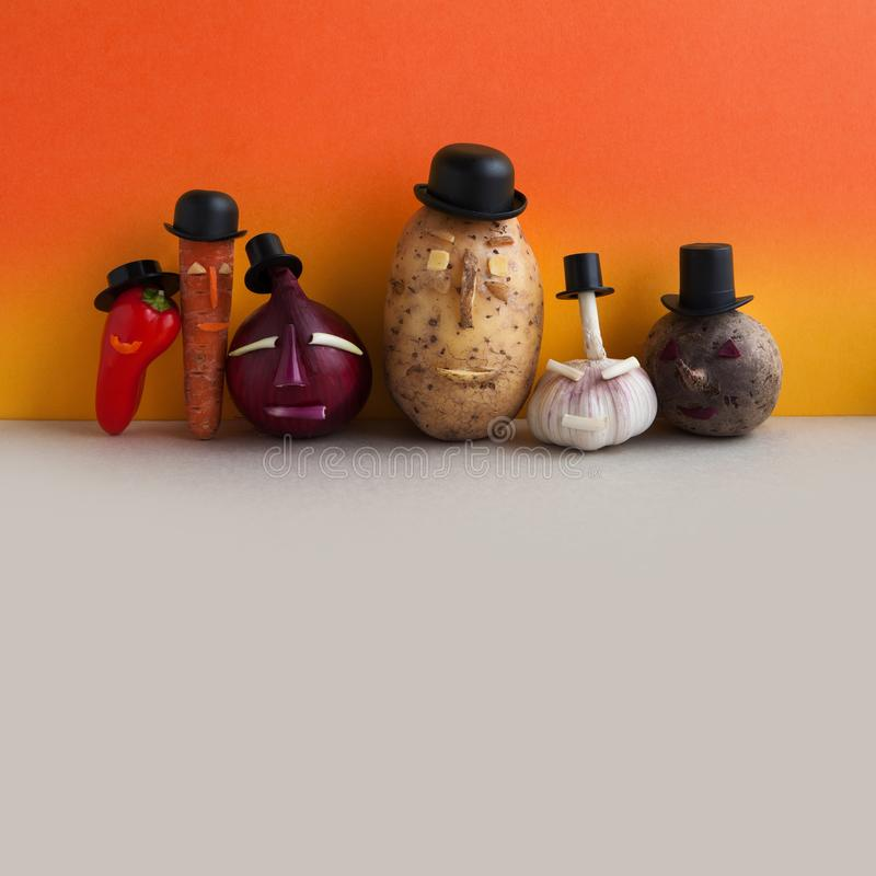 Funny vegetables team. Mister potato red onion beetroot garlic pepper carrot. Old fashion style characters organic. Plants, faces black hats. Orange yellow wall stock photos