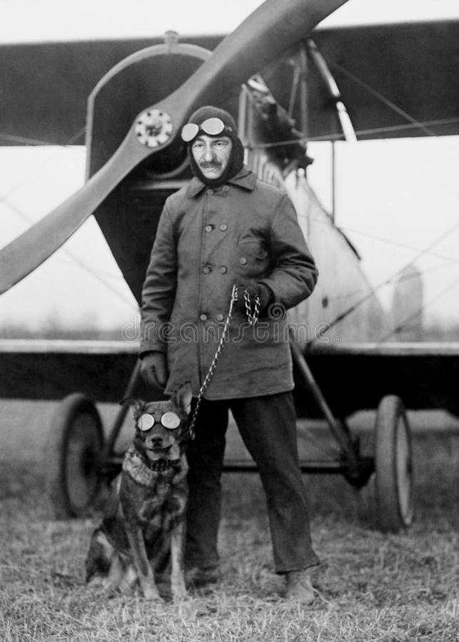 Funny Vintage Aviator pilot, Dog, Aviation. Funny vintage retro biplane airplane pilot. The aviator has a dog wearing goggles. Old aviation scene royalty free stock photography