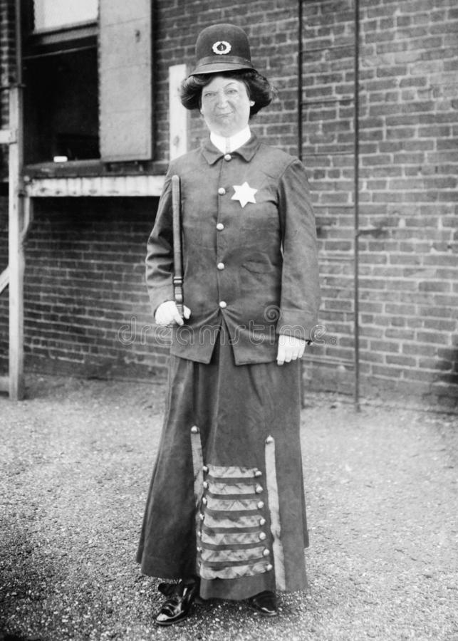 Funny Vintage Cop, Police, Policewoman, Woman. Funny vintage retro cop, police, or policewoman. The woman law enforcement officer has a serious and goofy look on stock photo
