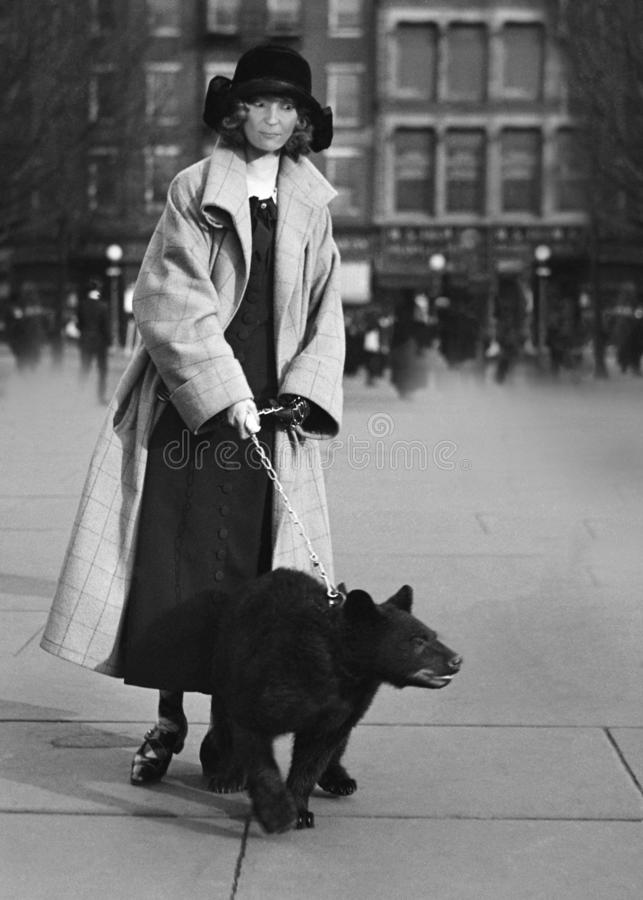 Funny Vintage Woman Walking Bear in City royalty free stock photo