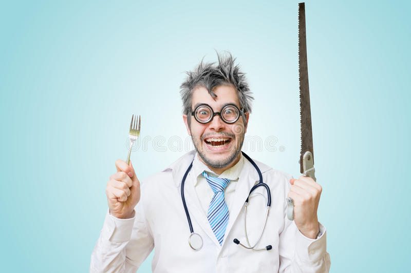 Funny wacky and crazy surgeon doctor holds unusual instruments royalty free stock images