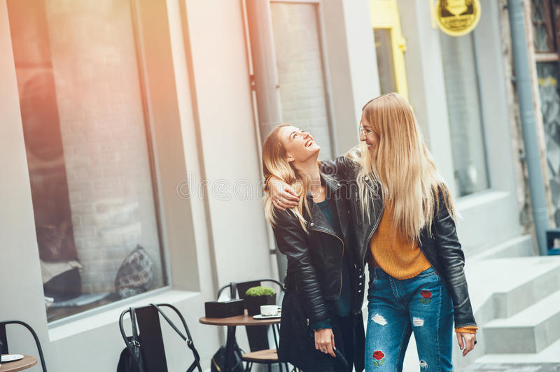 It is funny walk with best friend! Two beautiful women walking outdoor hugging and laughing on autumn street. stock photo