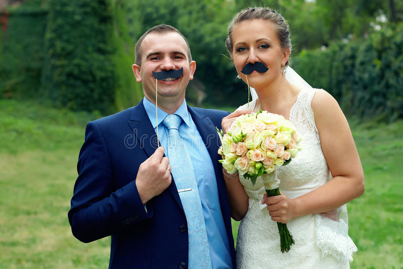Funny wedding couple with false mustache. Outdoors royalty free stock images