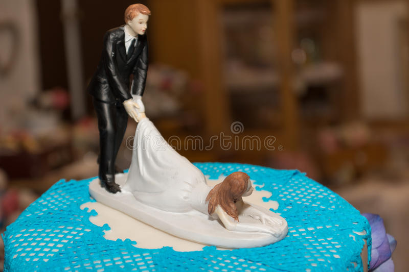 Funny wedding couple on wedding cake stock photo