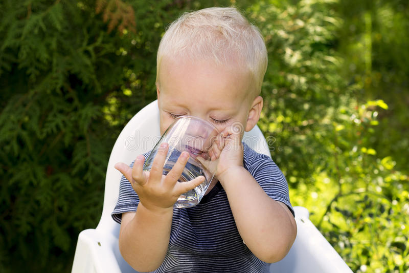 Funny wet baby boy trying to drink water from the glass independently royalty free stock image