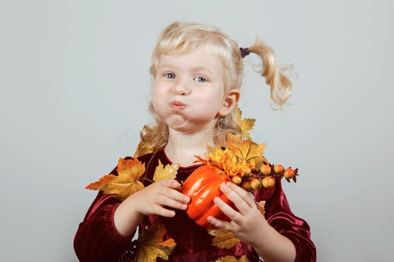 Funny white blonde Caucasian girl dressed with autumn yellow leaves for Halloween royalty free stock images