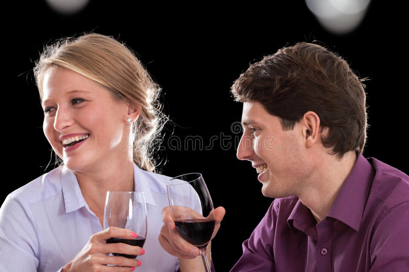 Funny wine conversation. A couple laughing having a funny conversation while drinking red wine stock photos