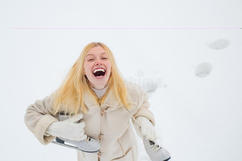 Funny winter girl is going skate outdoors. Beauty Joyful Girl having fun in winter park. Girl playing with snow in park royalty free stock images