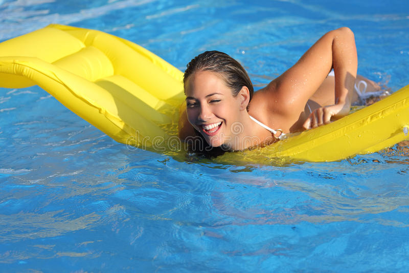 Funny woman bathing in a pool playing with a mattress stock photography