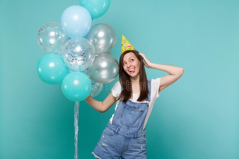 Funny woman in birthday hat showing tongue, looking up, put hand on head celebrating, hold colorful air balloons. Isolated on blue turquoise background royalty free stock image