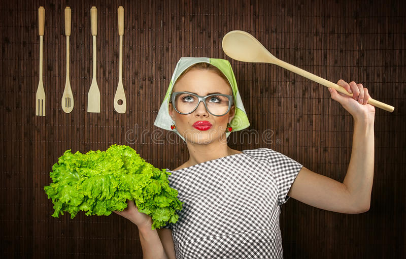 Funny woman cook. Funny rural woman cook holdin ledle and salad, close-up stock photos