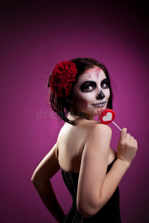 Funny woman in day of the dead skull face art. And heart sign candy stock photography
