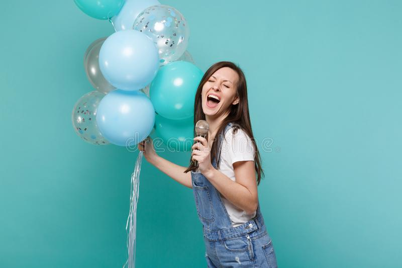 Funny woman in denim clothes with closed eyes sing song in microphone celebrating, holding colorful air balloons. Isolated on blue turquoise background stock image