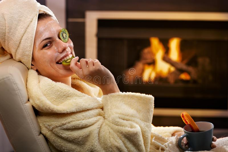 Funny woman eating fruit from facial mask stock photos