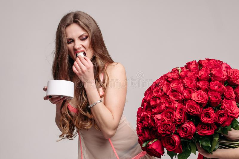 Funny woman eating sweets and running away from bouquet stock photo