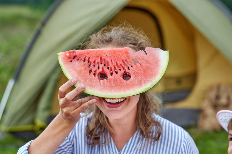 Funny woman eating watermelon on a picnic. Girl closed her eyes with a watermelon, looking into the holes royalty free stock photo