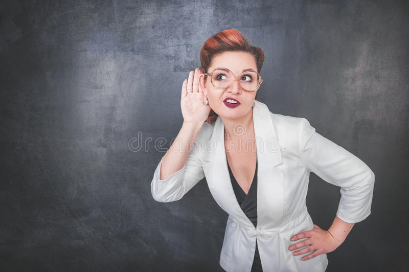 Funny woman eavesdrop on blackboard background stock photos