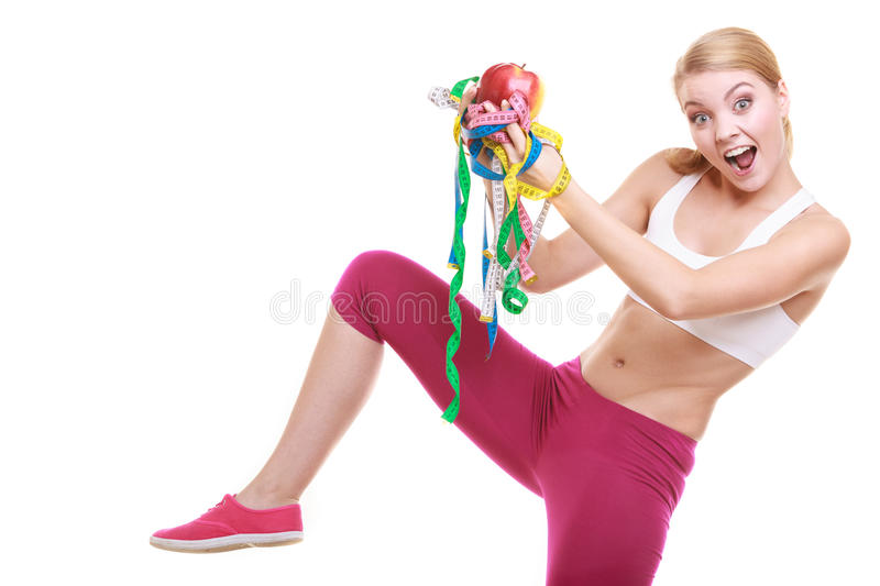 Funny woman holding apple and tape measures. Funny happy young woman girl holding apple and tape measures. Slimming and dieting. Healthy lifestyle nutrition royalty free stock photography