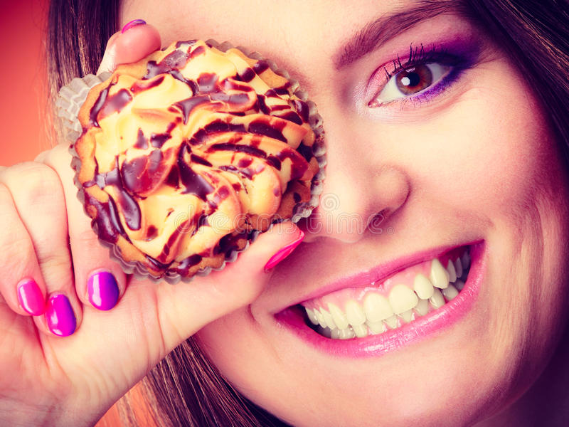Funny woman holds cake in hand covering her eye. Diet sweet food and people concept. Funny woman holds cake in hand having fun covering her eye with cupcake stock photo