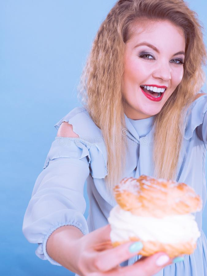 Funny woman holds cream puff cake. Sweet food and happiness concept. Funny joyful blonde woman holding yummy choux puff cake with whipped cream, excited face royalty free stock images