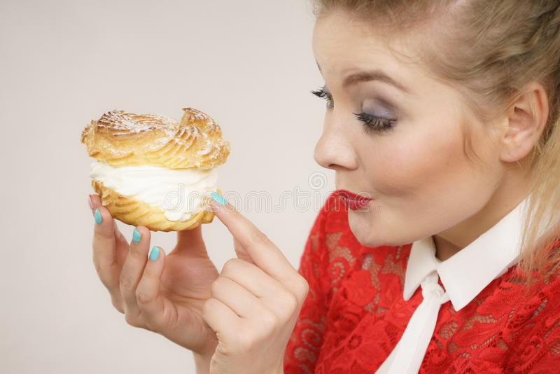 Funny woman holds cream puff cake stock photography
