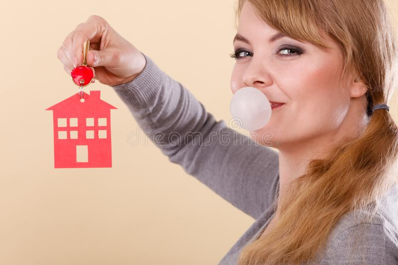 Funny woman holds house keys eat chewing gum. Young happy woman doing bubble with chewing gum while holding new house key with red home shape. Real estate royalty free stock photo