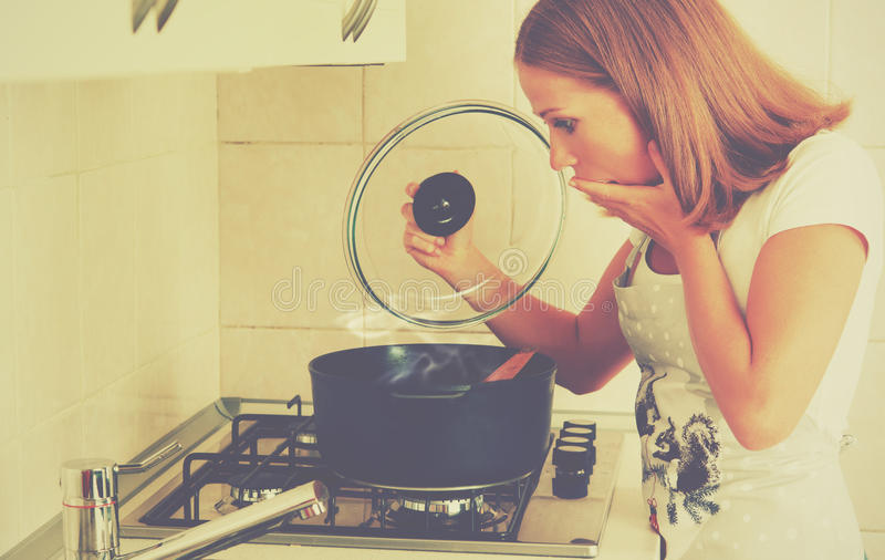 Funny woman housewife prepares in the kitchen royalty free stock images