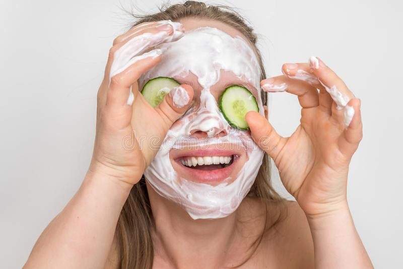 Woman with natural cream mask and cucumbers on her face stock images