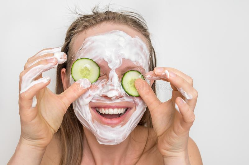 Woman with natural cream mask and cucumbers on her face stock photo