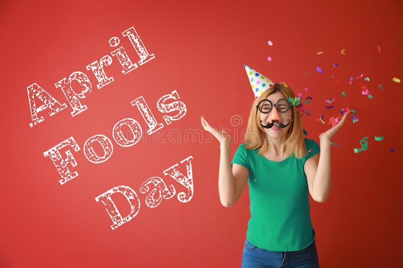Funny woman with party decor and confetti for April Fools\' Day on color background stock images