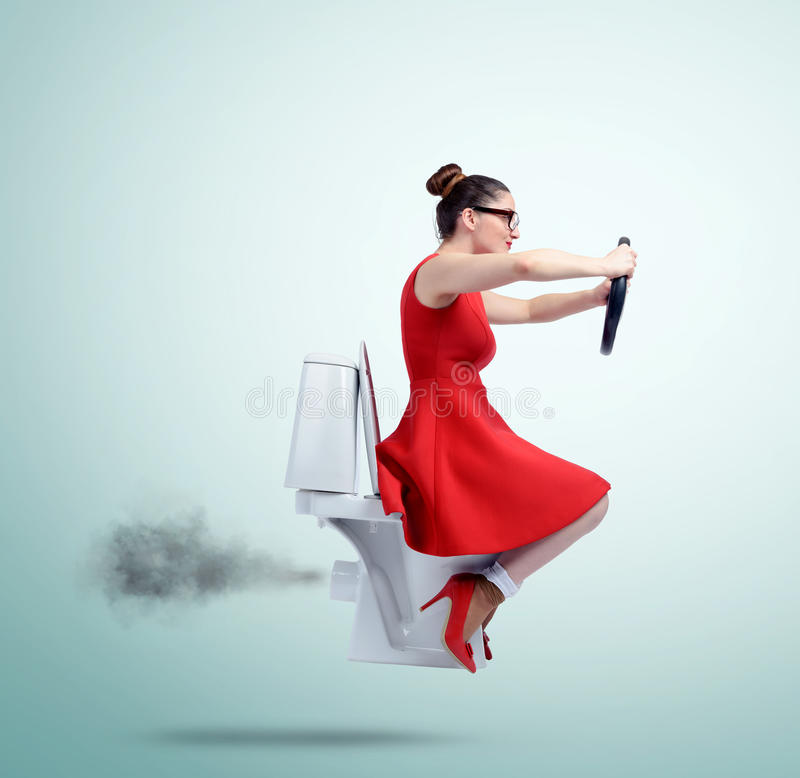Funny woman in red flying on the toilet with steering wheel. Concept of movement stock images
