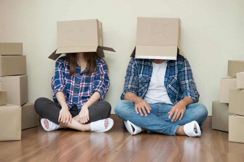 Funny woman and sad man move with cardboard boxes on their heads. Funny women and sad men move with cardboard boxes on their heads sitting on floor after at new royalty free stock photos
